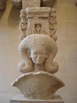 A sculpture of Hathor, an Egyptian deity wearing a curly omega shaped wig.